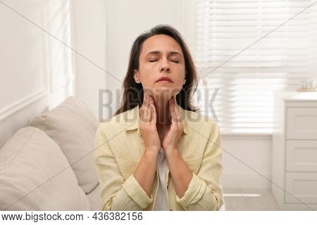 Mature Woman Doing Thyroid Self Examination At Home