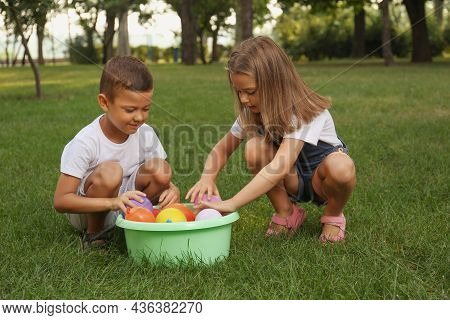 Little Children With Basin Of Water Bombs In Park