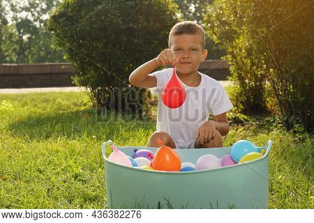 Little Boy With Basin Of Water Bombs In Park