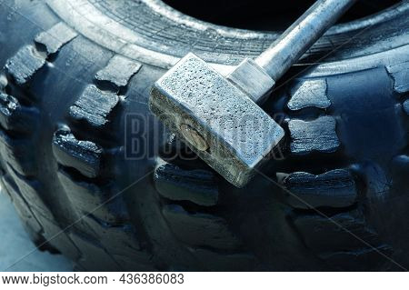 Hammer And Car Tire For Strength Training. Close-up