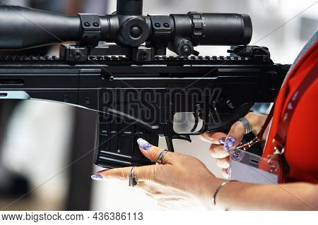 A Woman With A Manicure Is Holding A Firearm With A Telescopic Sight. Cropped Frame. Close-up