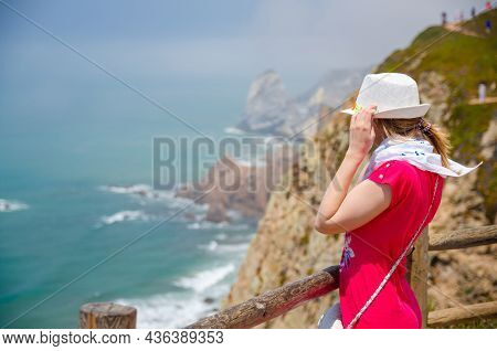 Young Woman Traveler With White Hat And Red Dress Staying Near Wooden Fence At Cliff Of Cabo Da Roca