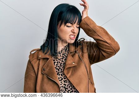 Young hispanic woman wearing casual leather jacket surprised with hand on head for mistake, remember error. forgot, bad memory concept.
