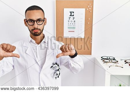 African american optician man standing by eyesight test pointing down looking sad and upset, indicating direction with fingers, unhappy and depressed.