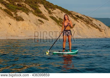 August 4, 2021. Anapa, Russia. Sporty Woman Paddle On Stand Up Paddle Board At Quiet Sea With Evenin