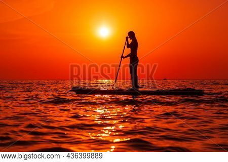 August 4, 2021. Anapa, Russia. Sporty Woman On Paddle Board At Quiet Sea With Colorful Sunset Or Sun