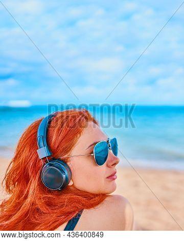 Redhead Woman Listening To Music On The Beach. Sexy Woman Listening To The Music On The Beach. The C