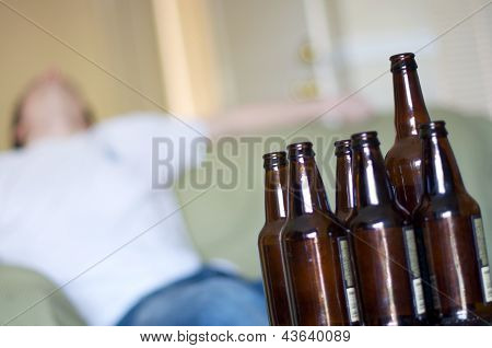 Man passed out on couch with empty beer bottles, angled