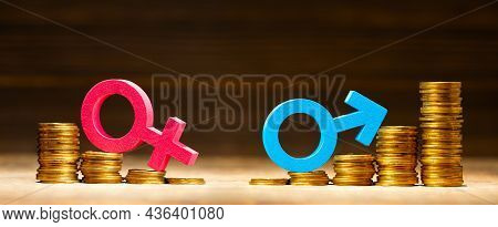 Stack Of Coins And Gender Symbols Male And Female. The Salary Of Men Is More
