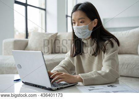 A Thoughtful Asian Woman In A Medical Mask Using A Laptop Is Working In The Living Room. Student Stu