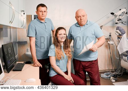 Dentists Team In Blue Work Shirts Studying Dental X-ray Or Orthopantomogram In Dental Office With Mo