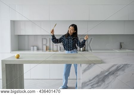 Smiling Beautiful Asian Woman In A Shirt And Jeans Dances In A Modern Kitchen, Cooks Healthy Food A
