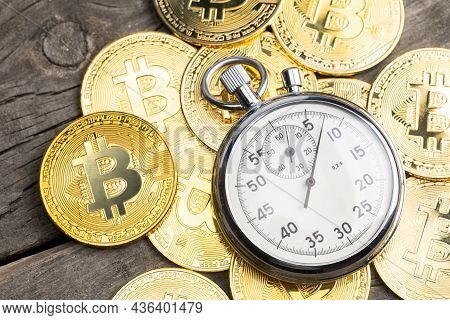 Stopwatch And Bitcoin. Gold Coins Of Cryptocurrency And A Clock On A Wooden Table