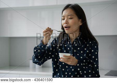 Young Asian Woman Eats Fresh Yogurt For Breakfast In The Kitchen