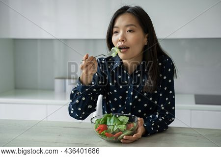Attractive Asian Woman Eats A Salad Of Fresh Vegetables. The Concept Of Diet And Healthy Eating.