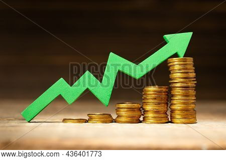 Green Arrow Graphic Upward And Stack Of Coins In Steps Upward As A Symbol Of Success
