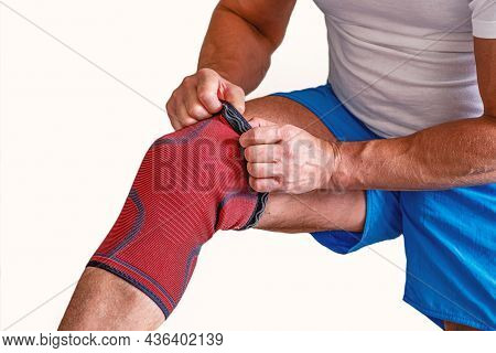 Man Adjusts A Compression Bandage On The Knee Joint. Sports Injury.