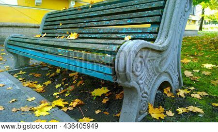 Fallen Dry Orange Yellow Maple Leaves On Lonely Empty Old Wooden Bench In City Street. Autumn Scene.