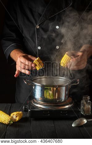 The Professional Chef Cooks Corn. Close-up Of A Cook Is A Hand While Cooking In A Restaurant Kitchen