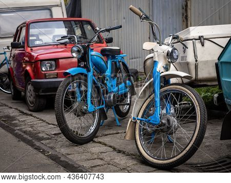 Wroclaw, Poland - September 19, 2021: Two Vintage Blue Komar Motorcycles And A Red 126 Fiat Car.