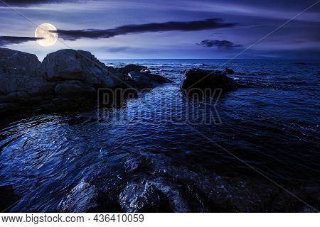 Sea Coast Scenery At Night. Boulders In The Calm Water. Few Clouds On The Sky In Full Moon Light. Lo