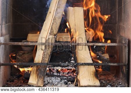 Firewood Is Burning In Fireplace Behind Metal Grate Closeup