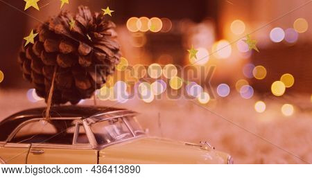 Image of christmas decoration with pine cone and model car over flickering fairy lights. christmas, tradition and celebration concept digitally generated image.