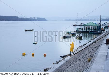 Belgrade, Serbia - January 31, 2016 Old Man, Fisherman Fishing On The Danube River During A Rainy Wi