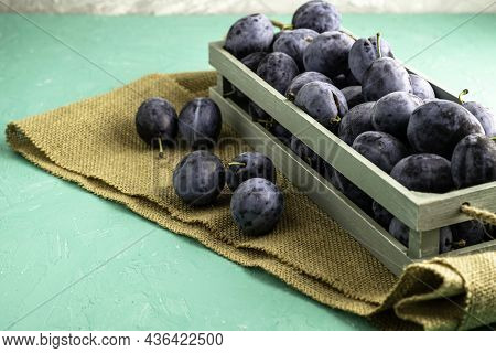 Freshly Picked Ripe Plum In A Vintage Box On A Piece Of Burlap Several Plums Lie Next To Each Other