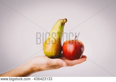Red And Green Apple And Pear Held In Male Hands. Conceptual For Comparison, Differentiation And Choi