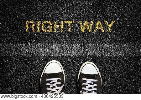 Right Way, On An Asphalt Road Surface, And Sneakers In Front Of The Lane Mark. Top View. Concept Of