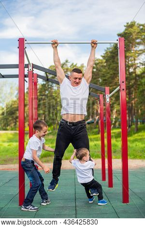 Caucasian Man And Two Boys Doing Exercises Outdoors. The Father Pulls Himself Up On The Horizontal B