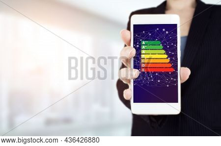Good Energy Chart Rating. Hand Hold White Smartphone With Digital Hologram Energy Efficiency Sign On