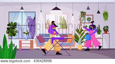 Lesbian Couple Ironing Clothes And Watering Plants Lgbt Transgender Love Housework Concept Living Ro