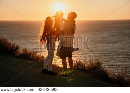 Silhouette Of A Young Romantic Couple With A Child Enjoying The Evening On A Cliff Above The Sea Wit