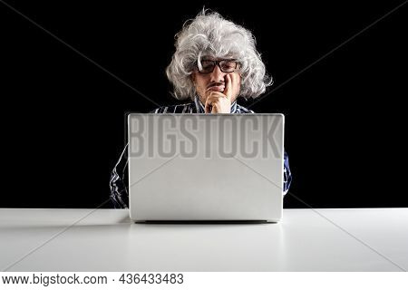 An Elder Serious Man Lost In Thoughts In Front Of A Laptop Computer, Focused Boomer Or Absent-minded