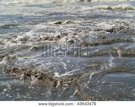 Sandy, Muddy Waves Rolling Onto The Shore That Resembles Floodwaters