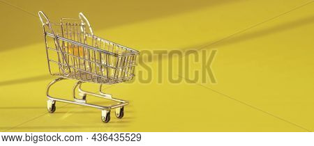 Shopping Cart On Yellow Bright Background With Day Light. Supermarket Trolley On Ad Banner With Copy