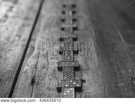 Domino Pieces On Wood Table. Concept Of Way Forward In Blurred Unpredictable Future.