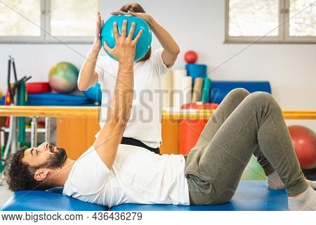 Male Patient And Female Physiotherapist At A Rehabilitation Center. Patient Doing Exercises With Sma