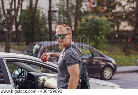 Mature Man, Handsome Courageous, 50 Years Old, Dressed In A T-shirt, Stands Near The Car And Holds A