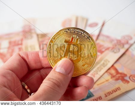A Man's Hand Holds A Gold Bitcoin. In The Background, Five Thousand Russian Ruble Bills. Cryptocurre