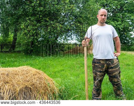 A Man Stands With His Back To The Camera With A Pitchfork In Front Of A Haystack. Rural Landscape, P