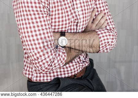 Torso Of Young Entrepreneur Wearing Plaid Shirt Casualy Leaning On Desk With Arms Crossed Against Gr