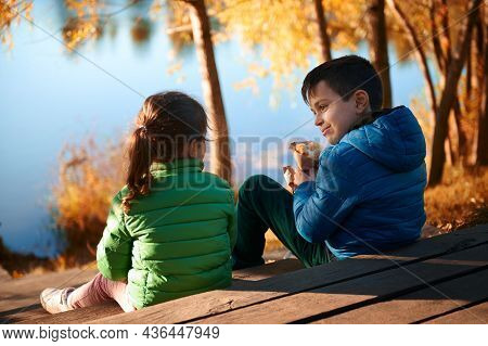 Two Adorable Preteen Beautiful Children Sitting On A Pier At River, Wearing Blue And Green Jackets A