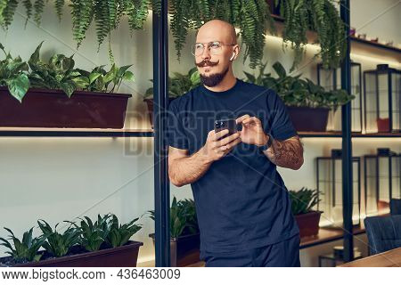 Thinking Businessman Trader Holds His Smartphone In A Hand Thinks About His Problems. Lost Money