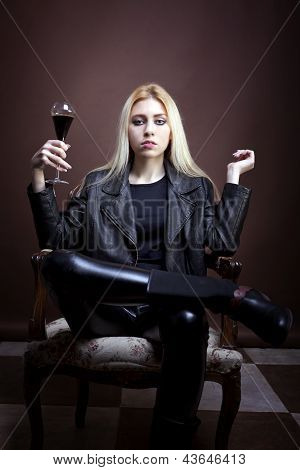 Rock Girl Holding A Glass With Dark Liquid