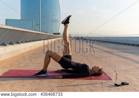 Side View Of Sportswoman Doing Glute Bridge Exercise With Raised Leg On Mat During Fitness Workout I