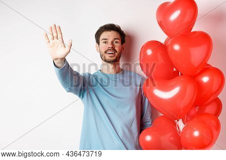 Handsome Young Caucasian Man Standing With Romantic Heart Balloon And Waving Hand At Lover, Waiting