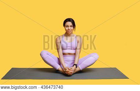 Calm African American Woman Doing Yoga Exercise, Sitting In Baddha Konasana, Bound Angle Or Butterfl